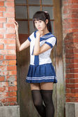 Asian schoolgirl in uniform outside school — Stok fotoğraf