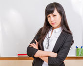 Asian teacher frowning in front of whiteboard — Stock Photo