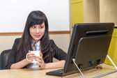 Portrait of Asian secretary sitting at desk — Stock Photo