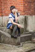 Asian schoolgirl sitting in front of school — Stock Photo