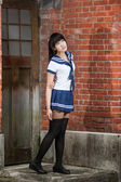 Asian schoolgirl standing in front of school — Stock Photo