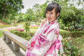 Asian woman wearing a yukata in Japanese style garden — Stock Photo