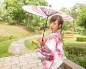 Asian woman wearing a yukata and holding an umbrella in Japanese — Stock Photo
