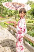 Asian woman in a yukata, holding an umbrella in Japanese style g — Stock Photo