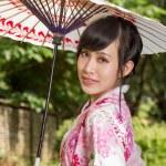 Asian woman wearing a kimono sitting in Japanese garden — Stock Photo #46570953