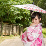 Asian woman wearing a kimono sitting in Japanese garden — Stock Photo #46570963