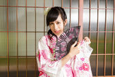 Asian woman wearing a kimono in front of Japanese wooden windows — Stok fotoğraf