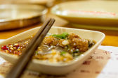 Chopsticks on spice dish with Chinese menu underneath — Stock Photo