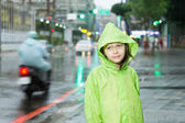 Young girl standing in rain with green raincoat — Stock Photo
