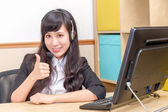 Asian operator giving thumbs-up at desk — Stock Photo