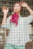Asian woman behind a metal fence — Stock Photo