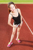 Chinese female athelete stretching on sports field — ストック写真