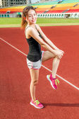 Chinese female athelete stretching legs on sports field, warming — Stock Photo