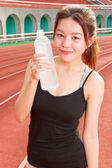 Chinese woman drinking water after jogging — Stock Photo