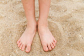 Child's bare feet in sand — Stock Photo