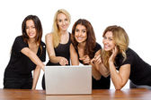 Group of girls pointing at a laptop — Stock Photo