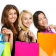 Three Girls with shopping bags over their shoulder — Stock Photo