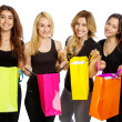 Four girls looking into shopping bags — Stock Photo