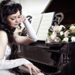 Bride longs at piano — Stock Photo #29694719