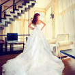 Beautiful bride in white dress in the living room — Stock Photo