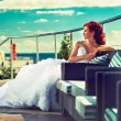Bride in white dress sitting outdoors — Stock Photo