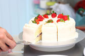 Hand holding milk cake with topping  strawberry. — Stock Photo
