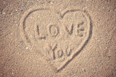 Writing heart on sand in valentines — Stock Photo