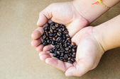 Hand giving coffee beans — Stock Photo