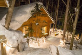 Log cabins glowing in the dusk surrounded by snow — Stock Photo