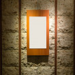 Blank wooden frame on stone wall illuminated spotlights in inter — Stock Photo #45701279