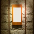Blank wooden frame on stone wall illuminated spotlights in inter — Stock Photo