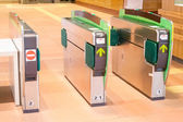 Turnstiles in underground railway station. Green arrows pointing — Stock Photo