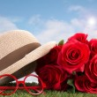 Red roses and glasses on green grass with blue sky — Stock Photo #46248931