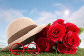 Red roses and glasses on green grass with blue sky — Stock fotografie