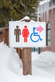 Restroom sign in the snow — Foto de Stock