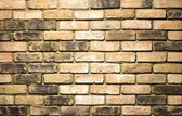 Vibrant yellow brick wall as a background image with vignette — Stock Photo