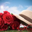 Red roses and glasses on green grass with blue sky — Stock Photo #46883603
