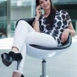 Very attractive young girl sitting on a white chair with a smartphone in hand — Stock Photo