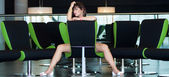 Young beautiful woman sits on chair in business room — Stock Photo