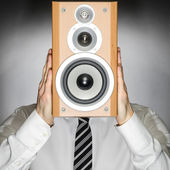 Man with speaker in front of face — Stock Photo