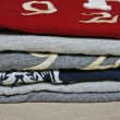 Stock Photo: Stack of colorful t-shirts on beige background