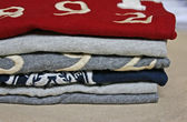 Stack of colorful t-shirts on beige background — Stock Photo