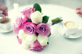 Beautiful bouquet of flowers on a table with cups of coffee — Stock Photo