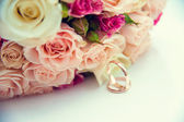 Wedding rings on roses background — Stock Photo