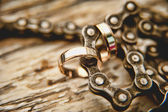 Wedding rings on the chain from the bicycle — Stock Photo