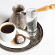 Freshly brewed coffee with a sweet on a plate — Stock Photo