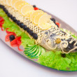 Stuffed pike decorated with slices of lemon and butter cream — Stock Photo