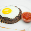 Grilled steaks, fried eggs and the sauce on white plate — Stock Photo