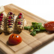 Three kebab on a grilled pita, served on a wooden plate with vegetables — Stock Photo