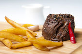 Potato fries with baked slice of veal on wooden dish — Stock Photo